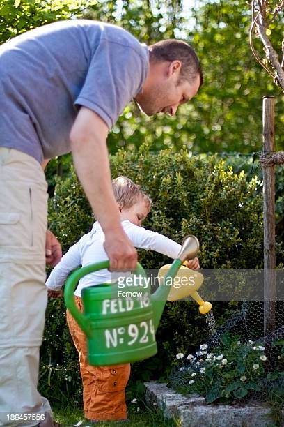 Toddler with father in garden watering flowers