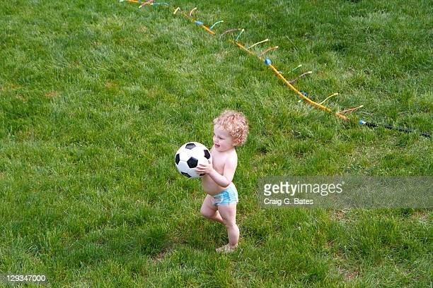 Toddler with soccer ball standing on grass