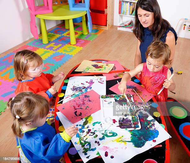 Toddlers Doing Art And Craft Under Carer's/ Childminder's Supervision