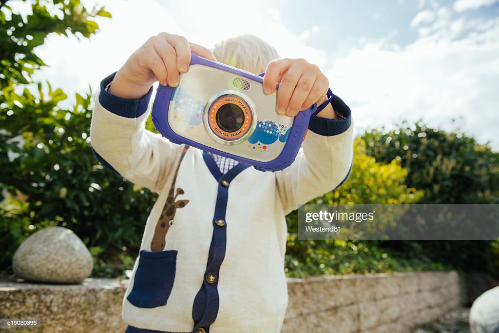 toddlers face hidden by childrens camera stock photo