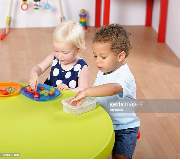 Toddlers/ Pre-schoolers Having Healthy Snack In A Nursery Setting