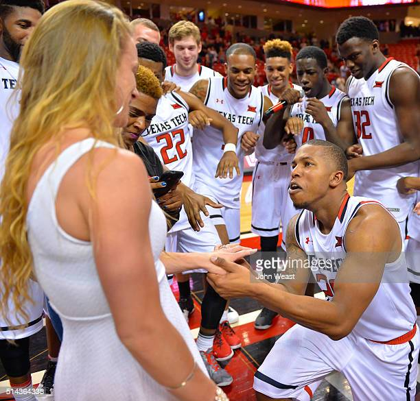 Toddrick Gotcher of the Texas Tech Red Raiders proposes to Kelly McQuaid as the Texas Tech Red Raiders look on after the game between the Texas Tech...