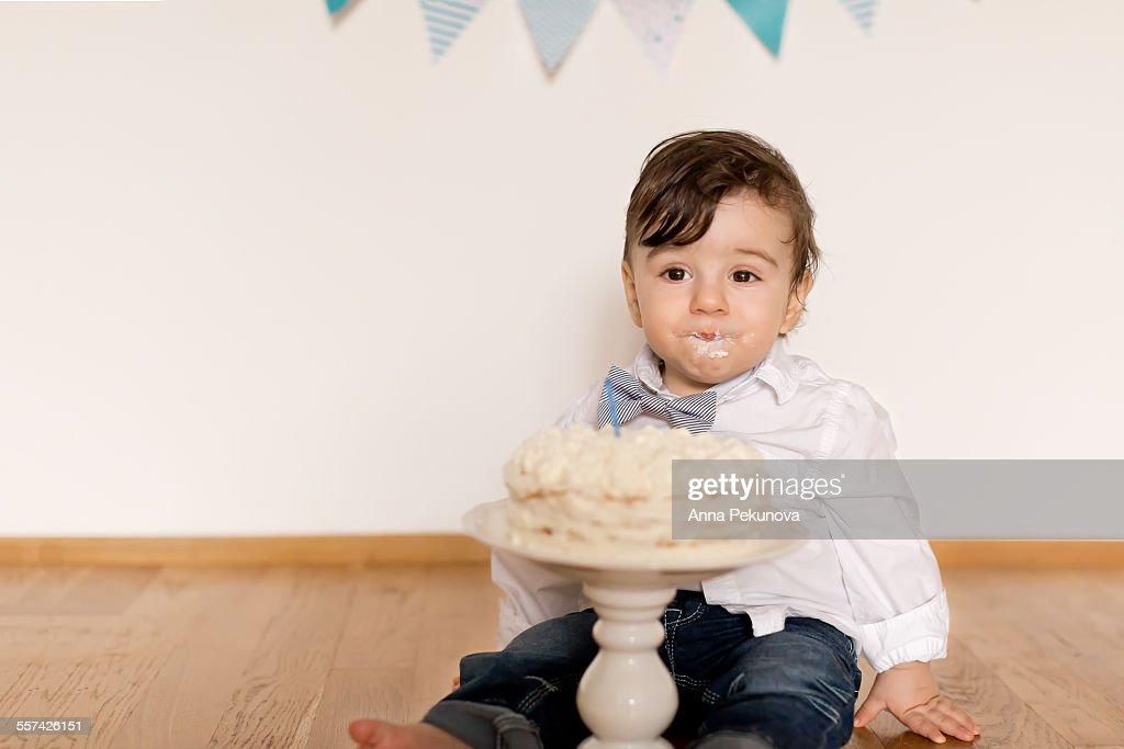 Todler boy behind birthday cake