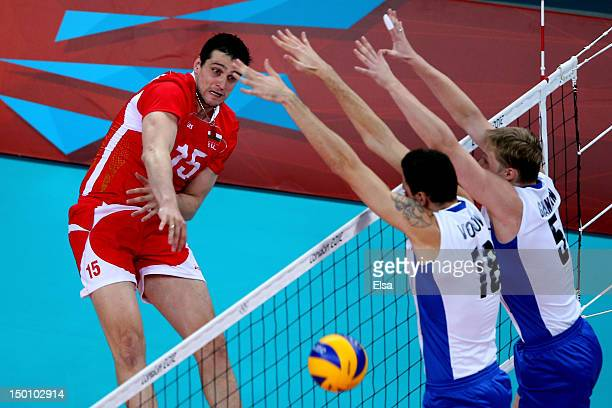 Todor Aleksiev of Bulgaria spikes the ball against Alexander Volkov and Sergey Grankin of Russia during the Men's Volleyball Semifinals on Day 14 of...