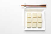 Tofu diced and served in a square plate, flat lay, view from above, space for a text