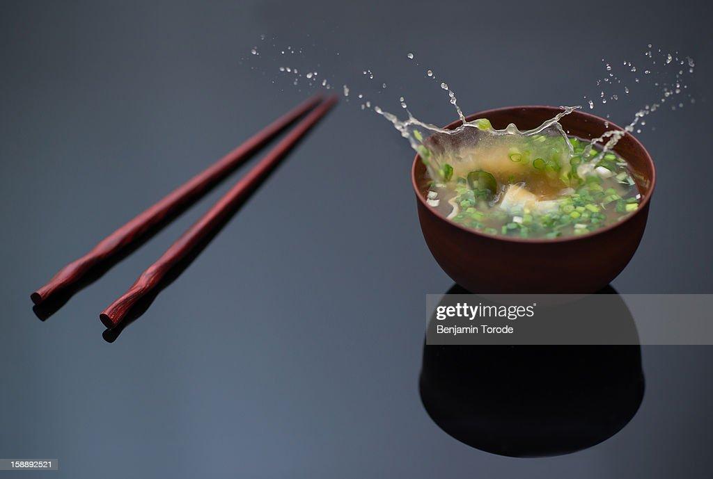 Tofu dropping into miso soup bowl : Stock Photo