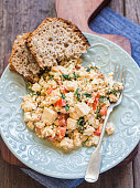 Vegan tofu scramble with tomato and green herbs served with wholegrain homemade bread. Wooden background.