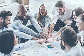 Group of happy business people holding hands together while sitting around the desk