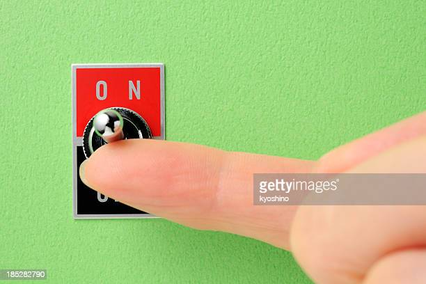 Toggle switch on green wall with index finger