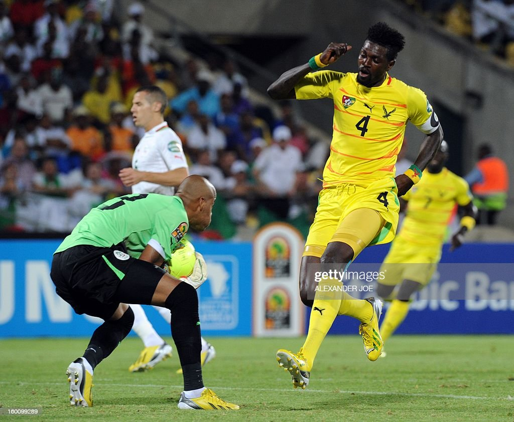 Togo Forward Emmanuel Adebayor (R) vies with Algerian goalkeeper Rais Mbolhi during the 2013 African Cup of Nations matc Togo-Algeria in Rustenburg on January 26, 2013 at Royal Bafokeng Stadium in a Group D match.