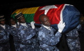 Togolese gendarmes carry the coffin wrapped in the national flag of one of the victims of the Forces for the Liberation of the State of...
