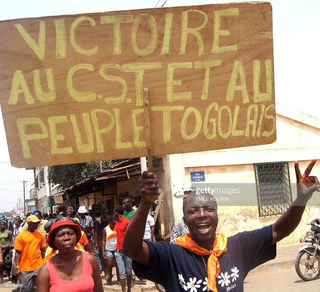 Togolese opposition members protest on February 16, 2013 in Lome, calling for the freeing of those arested in connection with the January 10 and 12 fires at major markets in the capital that the government has labelled criminal acts. Twenty-four people have been arrested in connection with the fires at the Kara market and at the Adawlato market, including opposition figures. Placard reads: 'Victory to the CST (the opposition Let's Save Togo coalition) and to the people of Togo'.