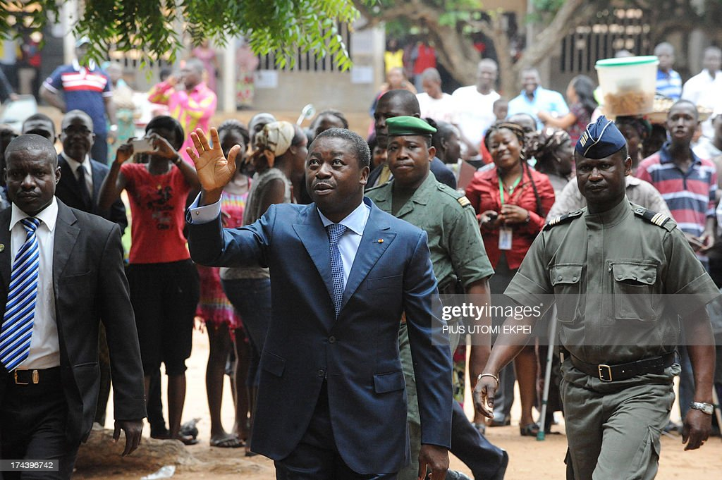 Togolese President Faure Gnassingbe (C) waves to the crowd as he arrives to cast his vote during the parliamentary election in Lome on July 25, 2013. Voters in Togo queued up Thursday to cast ballots in parliamentary elections delayed by months of protests, with the opposition seeking to weaken the ruling family's decades-long grip on power. Roughly two hours after polling stations opened, the most prominent opposition leader in the west African nation voiced concern over some initial hiccups, but said he was confident the vote would be clean. AFP PHOTO / PIUS UTOMI EKPEI