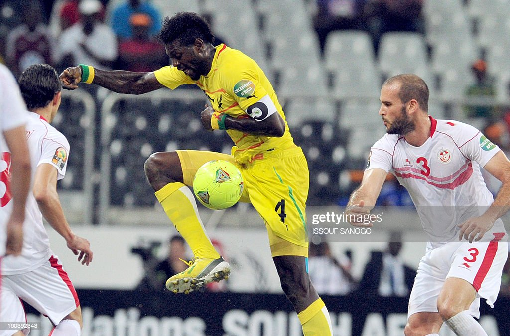 Togo's forward Emmanuel Adebayor (C) vies with Tunisia's defender Walid Hichri (R) during the Africa Cup of Nations 2013 group D football match Togo vs Tunisia on January 30, 2013 at the Mbombela stadium in Nelspruit. Togo drew 1-1 with Tunisia today to complete the Africa Cup of Nations quarter-final cast list and send the Carthage Eagles heading back to Tunis. AFP PHOTO / ISSOUF SANOGO