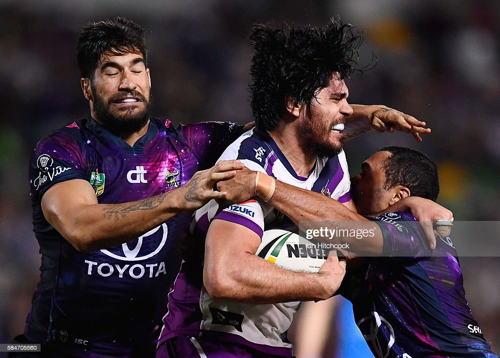 Tohu Harris of the Storm is tackled by Justin O'Neil and James Tamou of the Cowboys during the round 21 NRL match between the North Queensland Cowboys and the Melbourne Storm at 1300SMILES Stadium on July 30, 2016 in Townsville, Australia.