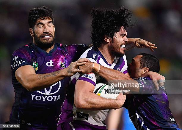 Tohu Harris of the Storm is tackled by Justin O'Neil and James Tamou of the Cowboys during the round 21 NRL match between the North Queensland...