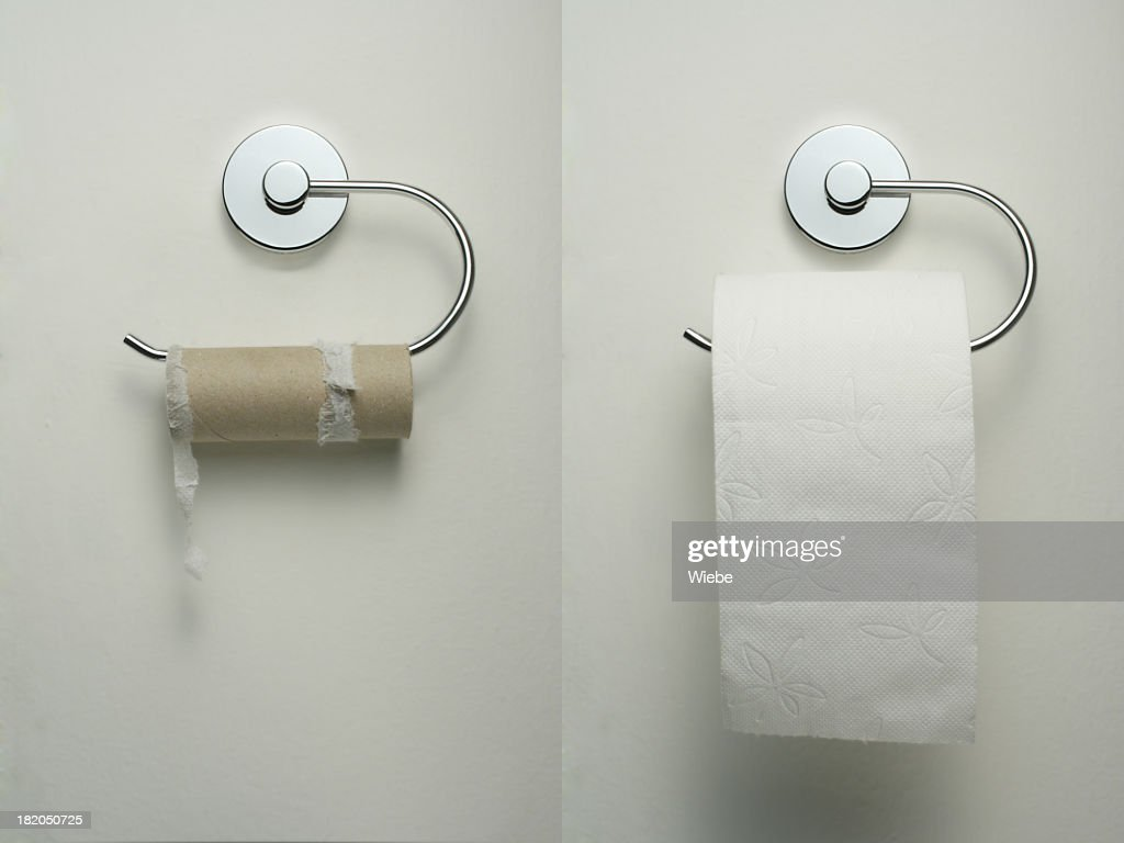 Toilet paper holder with empty and new roll hanging up : Stock Photo