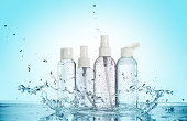 bottles of beauty products in a water splash isolated on blue background