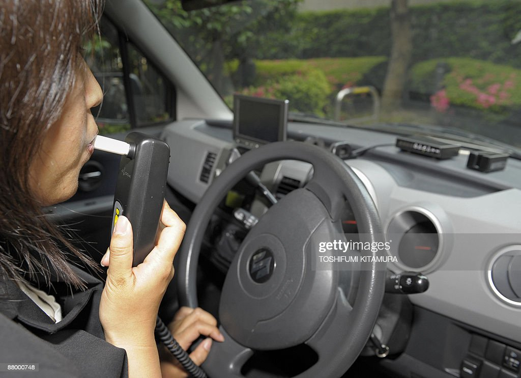 A Tokai Denshi employee demonstrates how to breath onto a sensor of the company's latest breath alcohol ignition interlock device called the...