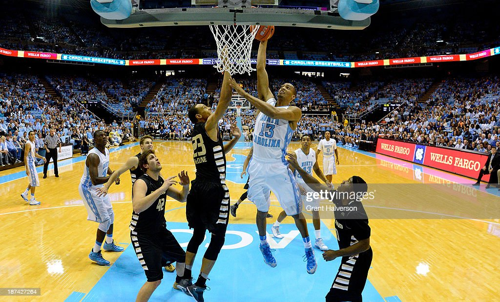 J.P. Tokoto #13 of the North Carolina Tar Heels drives in for a dunk over Tommie McCune #23 of the Oakland Golden Grizzlies during play at the Dean Smith Center on November 8, 2013 in Chapel Hill, North Carolina. North Carolina won 84-61.