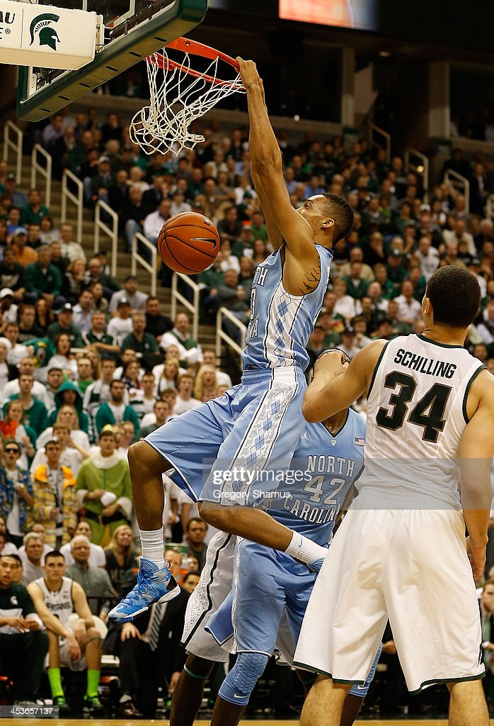 J.P. Tokoto #13 of the North Carolina Tar Heels gets in for a first half dunk behind Gavin Schilling #34 of the Michigan State Spartans at the Jack T. Breslin Student Events Center on December 4, 2013 in East Lansing, Michigan. North Carolina won the game 79-65.