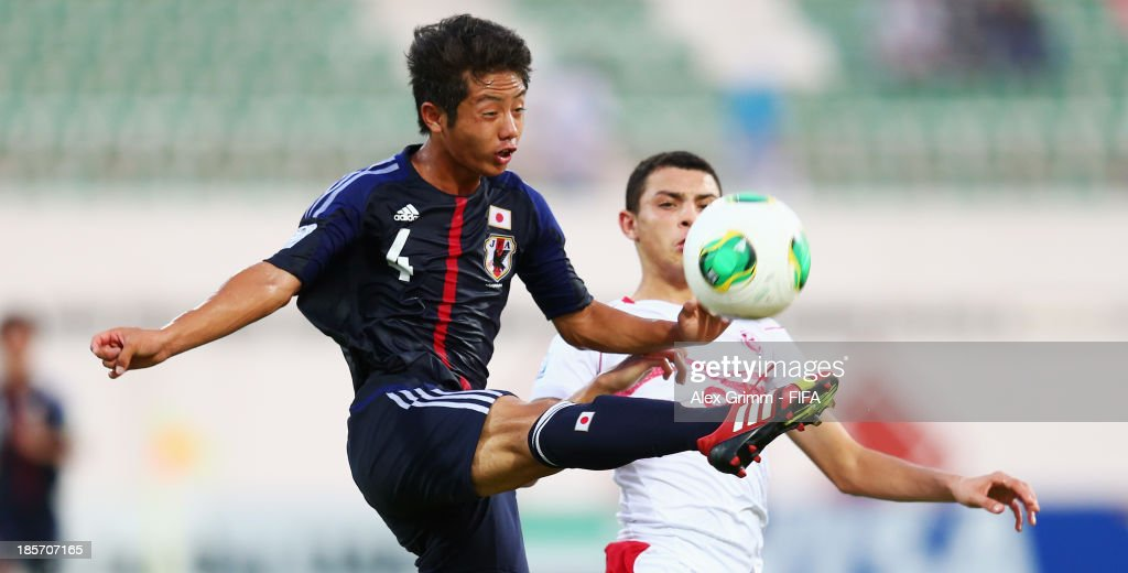 Tokuma Suzuki (front) of Japan is challenged by Chiheb Jbeli of Tunisia during the FIFA U-17 World Cup UAE 2013 Group D match between Japan and Tunisia at Sharjah Stadium on October 24, 2013 in Sharjah, United Arab Emirates.
