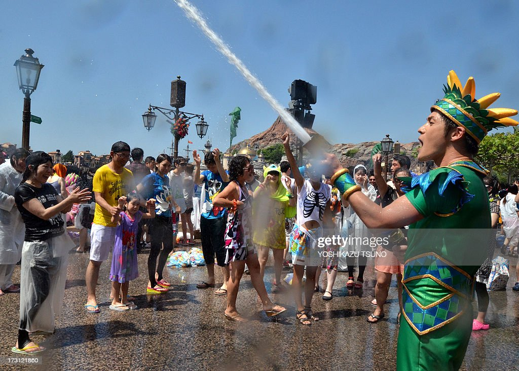 A Tokyo DisneySea cast member (R) uses a hose to spray water to spray water towards guests during a special summer attraction called 'Minnie's Tropical Splash' at Tokyo Disney Sea in Urayasu, suburban Tokyo on July 8, 2013. Tokyo's temperatures climbed 35 degrees Celsius as the rainy season in Tokyo metropolitan area ended, the Japan Meteorological Agency announced on July 6. AFP PHOTO / Yoshikazu TSUNO