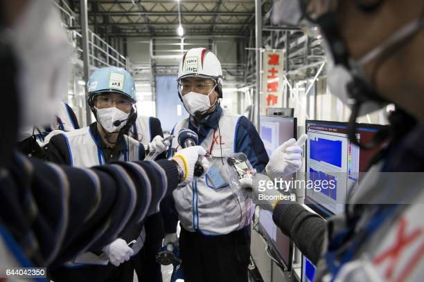 A Tokyo Electric Power Co employee center speaks to the media in front of a monitor in the frigerator building at the company's Fukushima Daiichi...