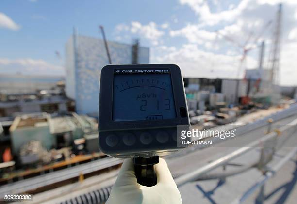 A Tokyo Electric Power Co employee measures a radiation level of 213 micro Sievert per hour in front of the No 2 and No3 reactor buildings during a...