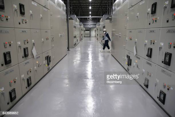 A Tokyo Electric Power Co employee walks through the electric control room of the 'refrigerator' building at the company's Fukushima Daiichi nuclear...