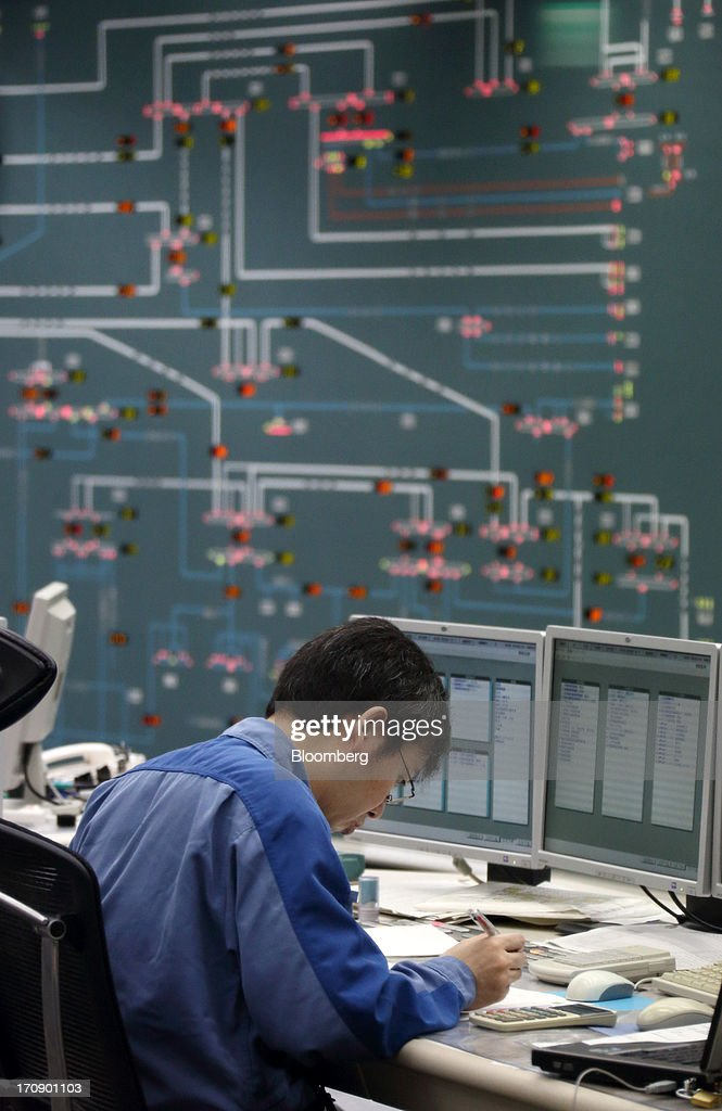 A Tokyo Electric Power Co. (Tepco) employee works at the company's central grid management center in Tokyo, Japan, on Thursday, June 20, 2013. Tepco faces more than 11 trillion yen ($108 billion) in estimated costs, including compensation payments, after the quake and tsunami two years ago caused three meltdowns and radiation leaks, forcing about 160,000 people to evacuate. Photographer: Tomohiro Ohsumi/Bloomberg via Getty Images
