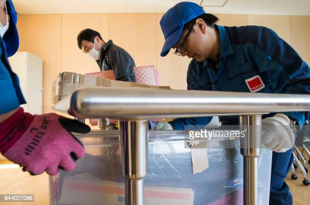 Tokyo Electric Power Co employees carry a box to a classroom as they help with preparations for the reopening of Narahamachi elementary school in...