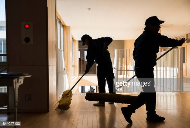 Tokyo Electric Power Co employees use floor mops as they help with preparations for the reopening of Narahamachi elementary school in Naraha...