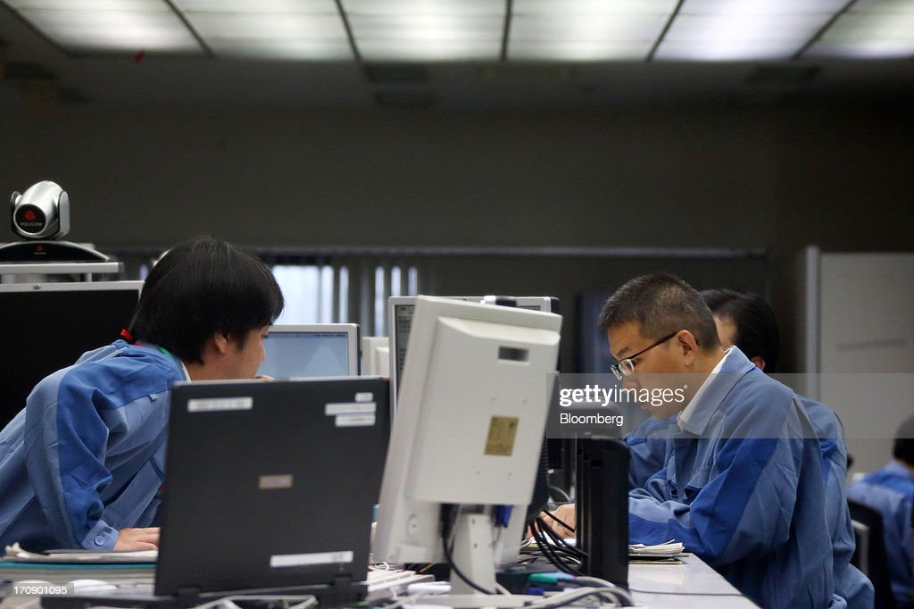 Tokyo Electric Power Co. (Tepco) employees work at the company's central grid management center in Tokyo, Japan, on Thursday, June 20, 2013. Tepco faces more than 11 trillion yen ($108 billion) in estimated costs, including compensation payments, after the quake and tsunami two years ago caused three meltdowns and radiation leaks, forcing about 160,000 people to evacuate. Photographer: Tomohiro Ohsumi/Bloomberg via Getty Images