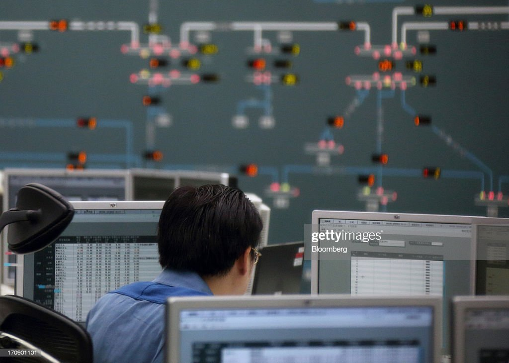 Tokyo Electric Power Co. (Tepco) employees work in the company's central grid management center in Tokyo, Japan, on Thursday, June 20, 2013. Tepco faces more than 11 trillion yen ($108 billion) in estimated costs, including compensation payments, after the quake and tsunami two years ago caused three meltdowns and radiation leaks, forcing about 160,000 people to evacuate. Photographer: Tomohiro Ohsumi/Bloomberg via Getty Images
