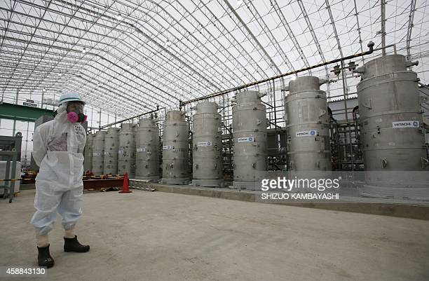 A Tokyo Electric Power Co official wearing radioactive protective gear stands in front of Advanced Liquid Processing Systems known as ALPS at the...