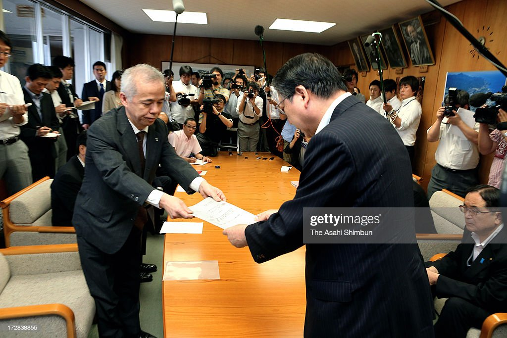 Tokyo Electric Power Co President Naomi Hirose (L) hands in the request to Kashiwazaki City Mayor Hiroshi Aida during their meeting at Kashiwazaki City Hall on July 5, 2013 in Kashiwazaki, Niigata, Japan.The president of Fukushima Nuclear Plant operator visits local governments seeking the understanding of the restart of their Kashiwazaki Kariwa Nuclear Power Plant.