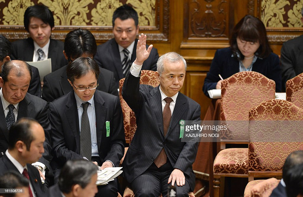 Tokyo Electric Power Co. (TEPCO) president Naomi Hirose (C) raises a hand to answer questions during a budget committee session of the lower house at parliament in Tokyo on February 12, 2013.