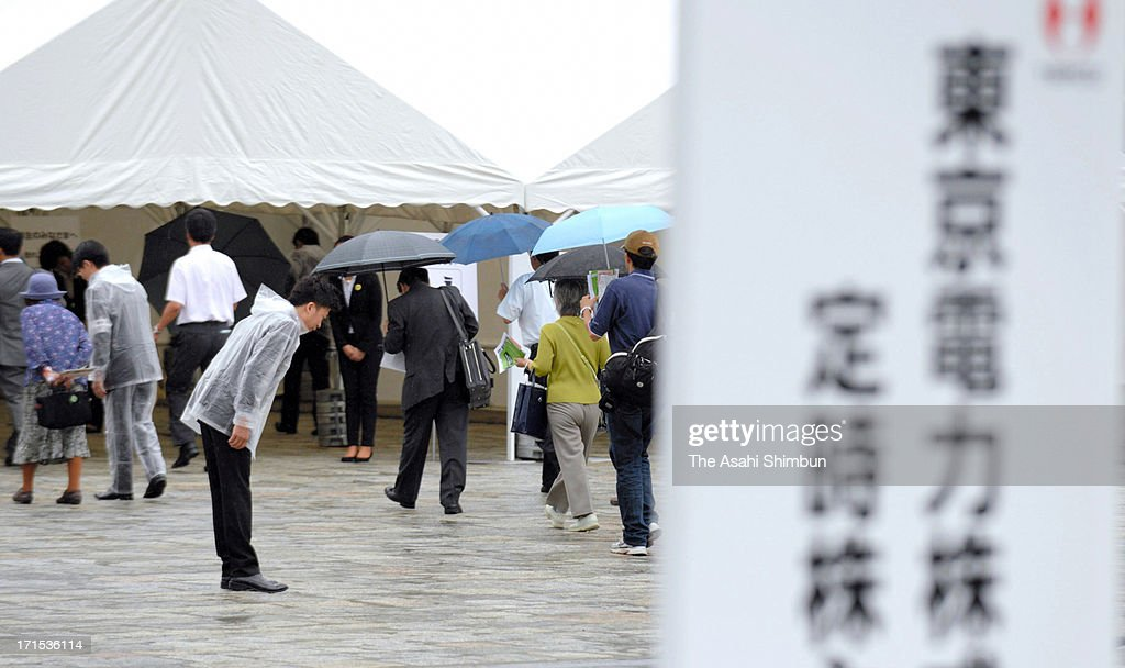 A Tokyo Electric Power Co staff bows to shareholders at the entrance on June 26, 2013 in Tokyo, Japan. Japan's all nine electric power companies hold shareholders meeting, denied 72 shareholders proposals of nuclear-free power generation, took clear stance of restarts of nuclear power plants in Japan.