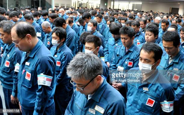 Tokyo Electric Power Co staffs observe a minute of silence to commemorate victims at the Fukushima Daiichi Nuclear Power Plant on March 11 2017 in...
