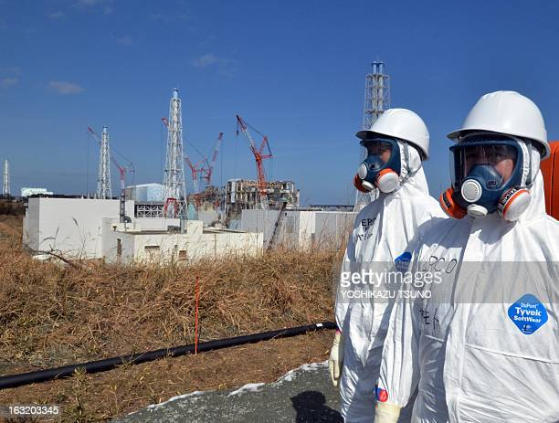 Tokyo Electric Power Co workers stand before stricken Fukushima Daiichi nuclear power plant at Okuma town in Fukushima prefecture northern Japan on...