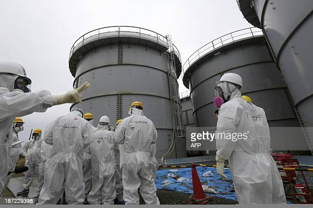 Tokyo Electric Power Corp's officials stand with journalists at the H4 tank area where radioactive water leaked from storage tank in August at the...