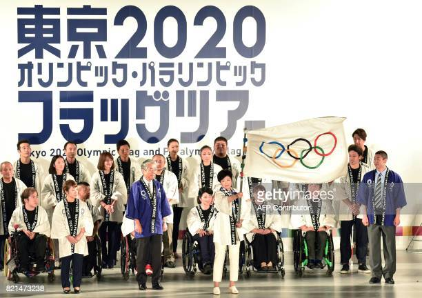 Tokyo governor Yuriko Koike waves the Olympic flag during a ceremony marking three years to go before the start of the Tokyo 2020 Olympic games at...