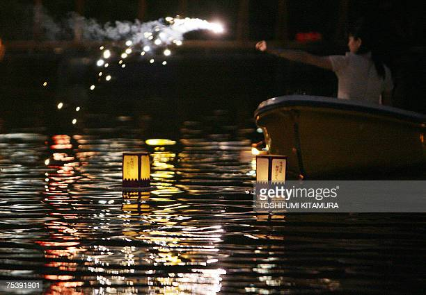 A Japanese woman lights a sparkler from from a boat as lanterns float beside her during the annual summer evening festival in Tokyo 13 July 2007 A...