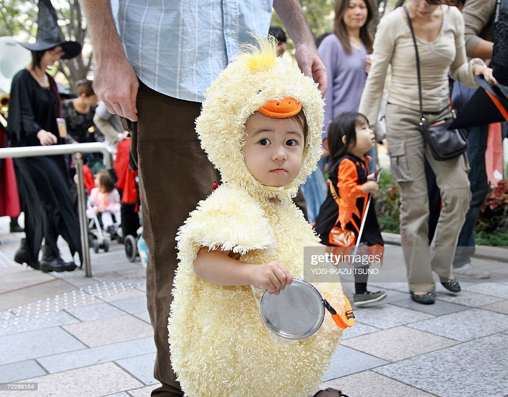 a little girl dressed as a baby chicken walks with children and their parents in costumes