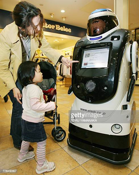 A mother and Child admire a guard robot 'Guardrobo D1' from Japan's Sogo Securities Service which is able to patrol inside a building and to guide...