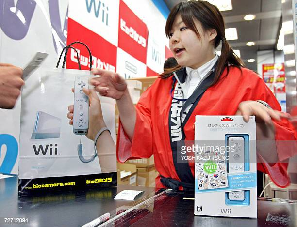A sales assistant pack Nintendo's new video game console 'Wii' for one of the first customers in Japan to it at a Tokyo electric shop 02 December...