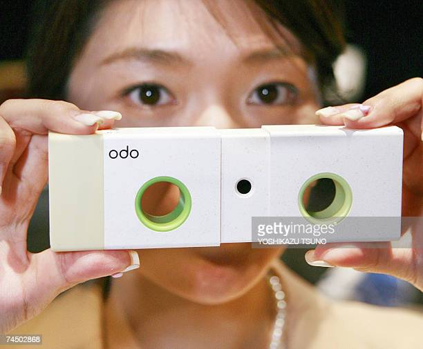 An employee of Japan's electronics giant Sony displays a prototype digital camera 'Spin N' Snap' which is a screenless digital camera which has two...