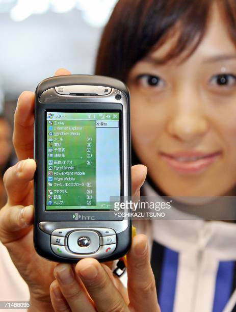 An employee of Japan's mobile communication giant NTT DoCoMo displays the new PDA shaped mobile handset 'htc Z' produced by Taiwanese maker HighTech...