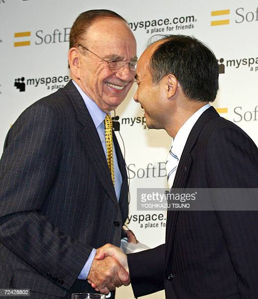 Australian media baron Rupert Murdoch Chairman and CEO of News Corporation shakes hands with Japanese Internet giant Softbank President Masayoshi Son...